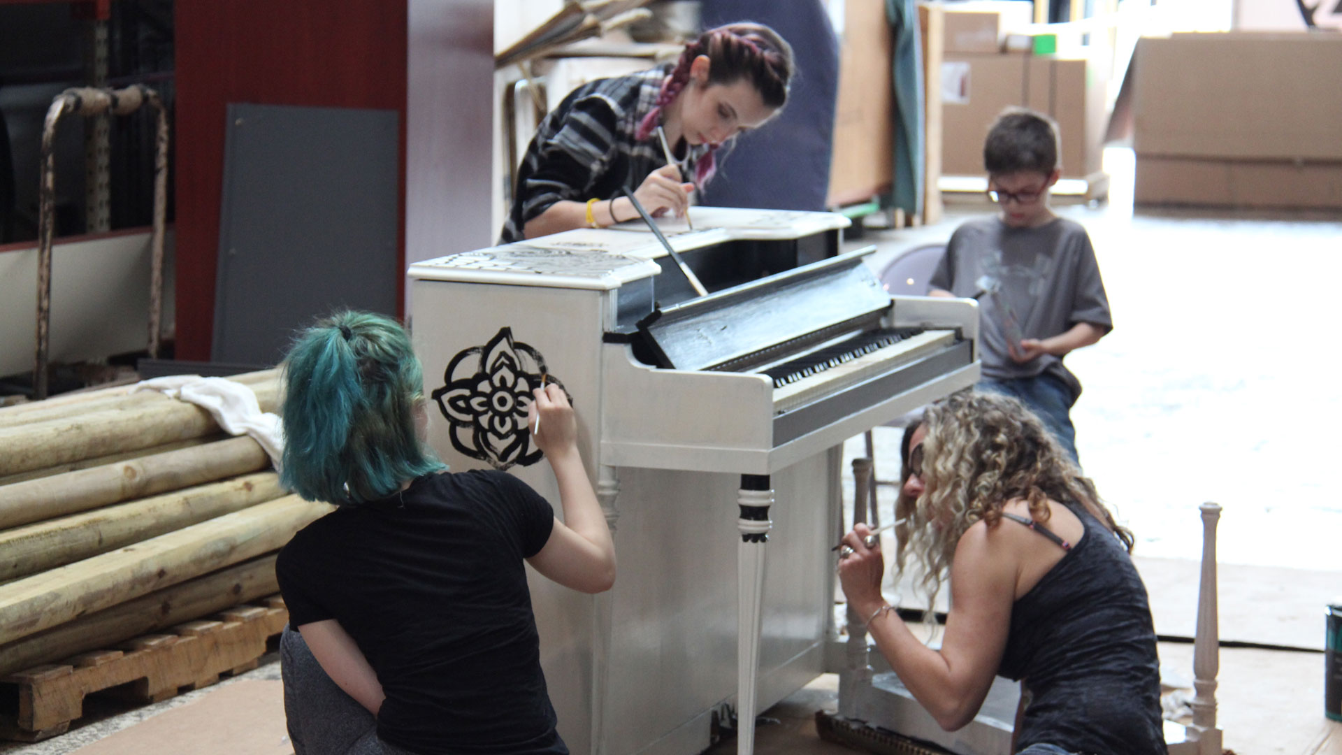 "Artists painting ""Zentangle"" theme on street piano inside Professional Movers.com Warehouse."